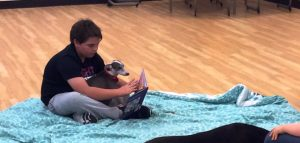 A young boy reading to a therapy dog sitting on a blue blanket.